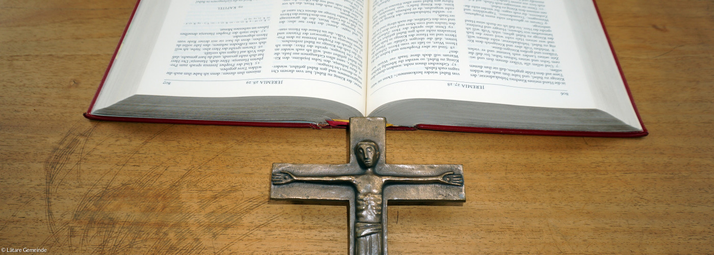 aufgeschlagene Bibel und Metallkreuz auf Altar