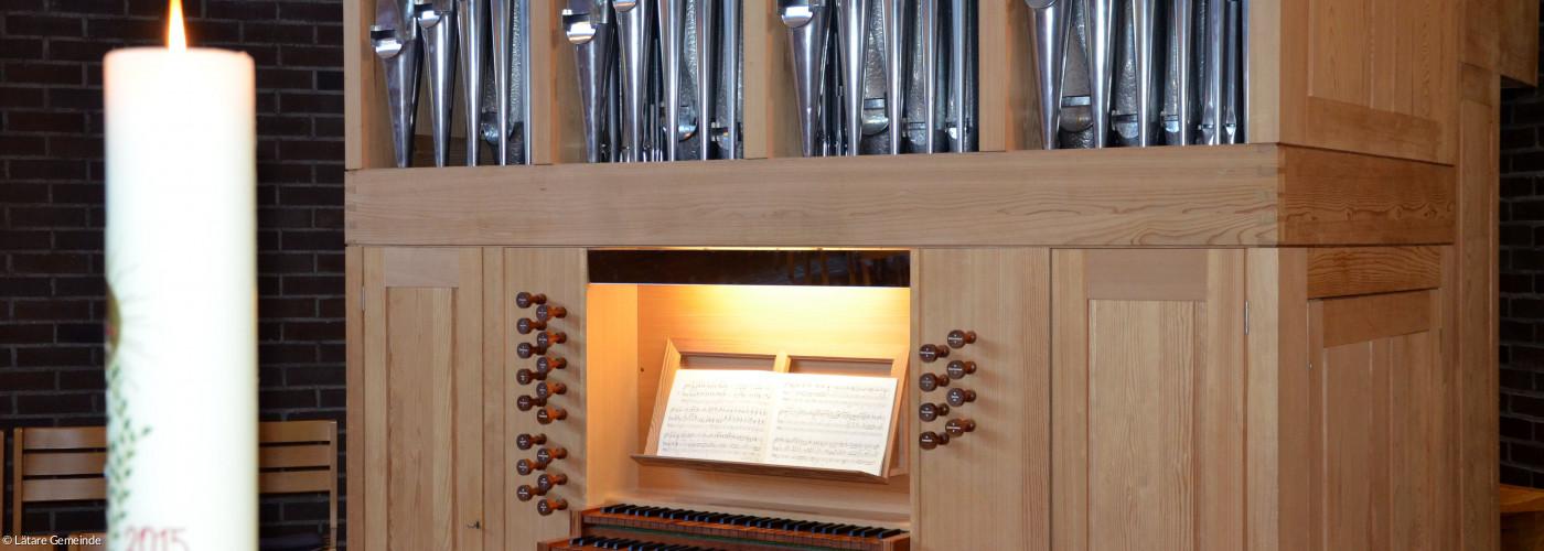 Blick auf die Orgel vom Altar aus mit Osterkerze im Vordergrund